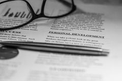 Personal development in a business text with glasses and a pen. Personal development highlighted in a educational text with glasses and a pen. Black and white Stock Photography