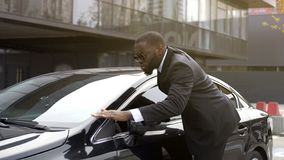 Personal driver of important person wiping dust from chic and shiny auto. Stock photo stock image