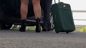 Personal driver opens the car door for business women with a suitcase near hotel. Personal driver opens the car door for business women with a suitcase and she stock footage