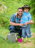 Personal example. Little helper in garden. Planting flowers. Growing plants. Take care of plants. Boy and father in royalty free stock photo