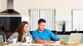 Personal expences. Young couple at the kitchen table, going over their expences, loans, financial situation and mortage statements Stock Images