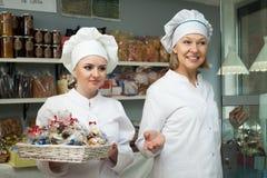 Personal femenino amistoso en los trajes blancos que ofrecen los dulces en confecti fotos de archivo libres de regalías