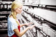 Personal femenino que comprueba productos del ultramarinos en estante fotografía de archivo