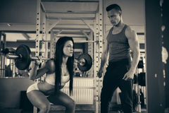 Personal fitness coach trains beautiful woman in gym Royalty Free Stock Image