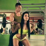 Personal fitness coach trains beautiful woman in gym Stock Images