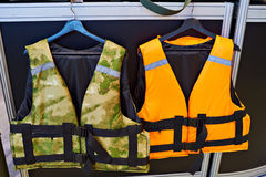 Personal flotation device as a life jacket in store. Orange and green royalty free stock photography