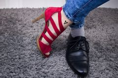 Personal has a lady`s boot on one foot, and on the other a male boot.The person has a third-gender tattoo. Man or woman? Person has woman´s red sandal and royalty free stock photos