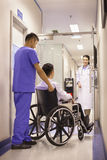 Personal hospitalario que empuja al paciente en silla de ruedas Fotografía de archivo libre de regalías