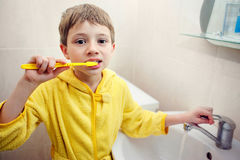 Personal hygiene. Care of an oral cavity. The boy brushes teeth. Stock Photos
