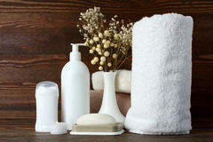 Personal hygiene products. Personal hygiene items with decorative sprigs on a brown wooden background Stock Photos