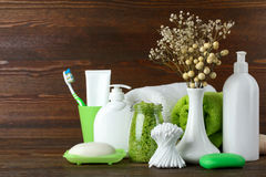 Personal hygiene products. Personal hygiene items with decorative sprigs on a brown wooden background Stock Image