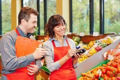 Personal i supermarket genom att använda mobilen arkivbild