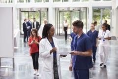 Personal i upptaget lobbyområde av det moderna sjukhuset arkivfoto