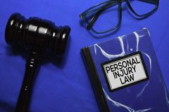Personal Injury Law text on Book and gavel isolated on office desk.