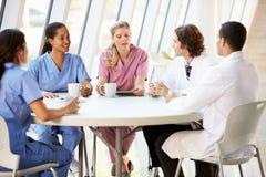 Personal médico que charla en cantina moderna del hospital imagen de archivo libre de regalías