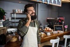 Personal masculino sonriente que habla en el teléfono móvil en el contador en cafetería fotos de archivo