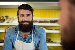 Personal masculino sonriente que se coloca en la tienda de carne foto de archivo