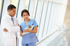 Personal médico que tiene discusión en pasillo moderno del hospital Imágenes de archivo libres de regalías