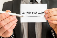 Personal motivator holding up a white card with a Go the distanc Royalty Free Stock Photos