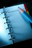 Personal organiser. Pencil on small personal organiser. Empty goals list under blue light Royalty Free Stock Image