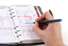 Personal organizer. A hand making notes in a personal organizer Royalty Free Stock Photography