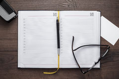 Personal organizer and pen with glasses on the table Royalty Free Stock Photos