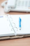 Personal organizer and pen on office desk Stock Photos