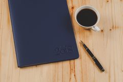 Personal organizer or planner with fountain pen. And hot coffee on wood table Royalty Free Stock Images