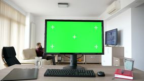 Personal PC computer with big green screen chroma mock up. On the table in the living room. A guy is entering the room in background while the TV is on and sits stock footage