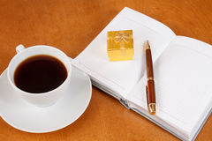 Personal planner with gift box, pen and cup of coffee Stock Images