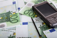 Personal pocket palmtop on money. Close-up Stock Photos