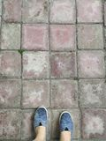 Personal point high angle view of wet gray shoes on red squre brick floor royalty free stock photos