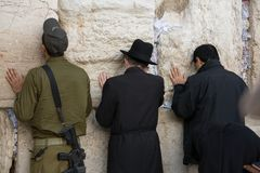 Personal prays. Praying soldier and men in Western Wall in Jerusalem Stock Images