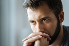 Portrait of an unhappy thoughtful man. Personal problems. Portrait of a sad unhappy thoughtful man while holding his chin and thinking about problems Royalty Free Stock Photography