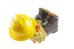 Personal protective equipment. Or PPE including leather boots, leather gloves, foam ear plugs, safety glasses, and yellow hard hat Royalty Free Stock Photography