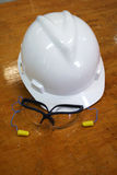 Personal protective equipment (PPE). Hardhat, clear safety goggles and earplugs on a table stock images