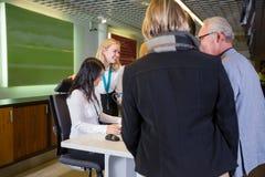 Personal que ayuda a pares mayores en el mostrador de facturación del aeropuerto Fotos de archivo libres de regalías
