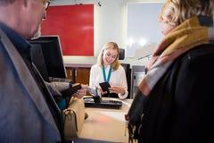 Personal que comprueba el pasaporte de pasajeros en el enregistramiento del aeropuerto imágenes de archivo libres de regalías