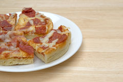 Personal size pepperoni pizza slices on a white plate. Several microwaved personal size pepperoni pizza slices on a white plate atop a wood table stock images