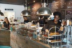 Personal som arbetar bak räknare i upptagen coffee shop royaltyfri bild