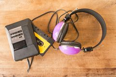 Personal stereo, cassette tape and headphones on a wooden board. Personal stereo with a cassette tape inside and headphones on a worn wooden board royalty free stock photos