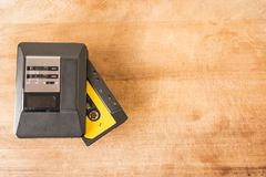 Personal stereo and cassette tape on a wooden board. Personal stereo with a cassette tape inside on a worn wooden board royalty free stock photo