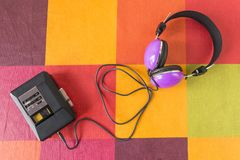 Personal stereo and headphones on a checkered tablecloth. Personal stereo with a cassette tape inside and headphones on a colorful checkered tablecloth royalty free stock photography