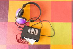 Personal stereo and headphones on a checkered tablecloth. Personal stereo with a cassette tape inside and headphones on a colorful checkered tablecloth stock images