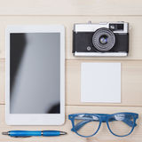 Personal things flat lay. Digital tablet, ball pen, eyeglasses, retro camera and notebook. Royalty Free Stock Photo