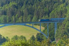 Personal train on a distant bridge over the valley. The railway bridge in the Czech Republic in the village of Dolni Loucky. Royalty Free Stock Photo
