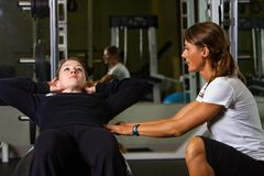 Personal Trainer. A trainer helping a woman do situps at the gym Stock Photo