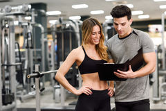 Free Personal Trainer And Client Looking At Her Progress At The Gym Royalty Free Stock Photos - 87423228