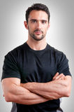 Personal Trainer. With is arms crossed, in a grey background stock photography