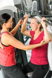 Personal trainer assist senior woman at gym Stock Images